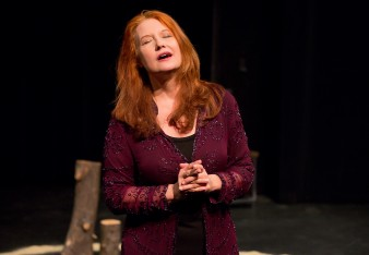 Performance artist, Karen Finley performing Written in Sand at Barbican. She has her hands clasped and her eyes closed.
