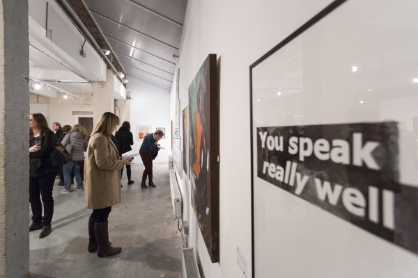 An exhibition shot from Shape Open 2016, a text based work in the foreground reads