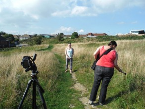 photo of two young women on a path in the countryside with a camera tripod standing in the shot