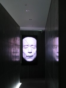 This black and white video portrait of Gao Zinglian in a dark narrow corrodor mirrors fuzzy purple in the rough polished concrete walls on each side of it. Gao Xinglian`s eyes are closed, his mouth very slightly open and his bald image is cropped at the c