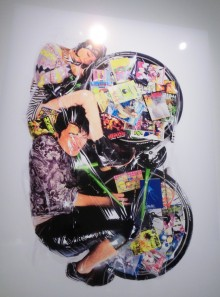 this picture of a shrink wrapped couple from the Image-Makers exhibition, shows two people curled around the wheels of a bicycle. The wheels are decorated with colourful printed cards, comics etc. the shimano gear wheel and a pedal are visible. The woman