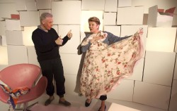photo of actress Julie McNamara holding a flowery dress close to herself, with a thumbs up from sign language interpreter Karl Lorca