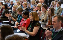 A photograph taken from Audio Description Association's National Conference which shows the crowd of delegates, many of them are clapping.