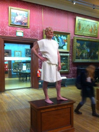 artist aaron williamson poses on a plinth in the walker art gallery, with a face covered in eyes