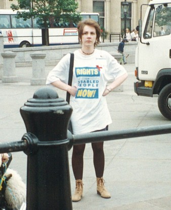 A photograph of Agnes Fletcher, she is wearing a disability rights t-shirt and has her hands on her hips.