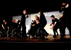 A photograph of Freewheelers Theatre Company's Amandla! featuring a group of performers all dressed in black and seemingly dancing, some standing, others in wheelchairs.