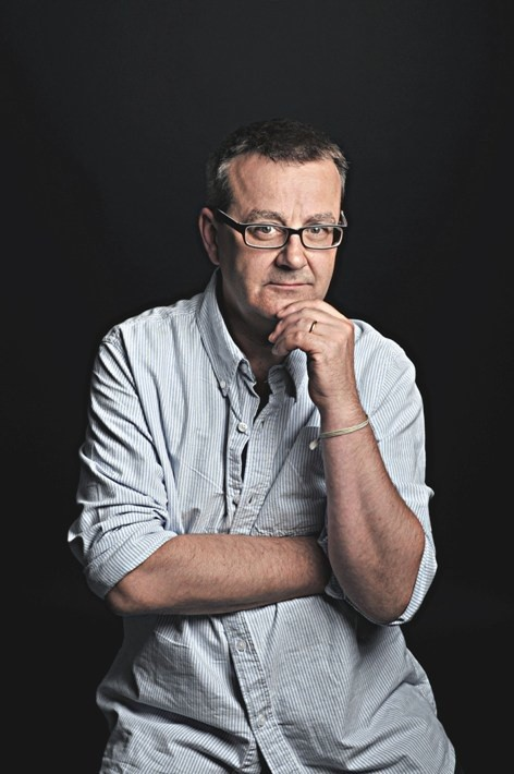 portrait photo of chris larner sitting thoughtfully in a chair against a black background
