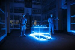 photo of two people dressed in surgeons costume standing in a room lit with a blue light
