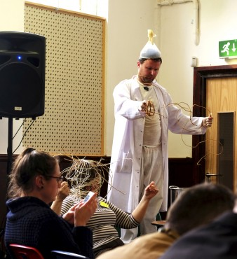 photo of performance artist Simon Raven wearing a white coat with a flask on his head, as he pulls a cane basket  apart