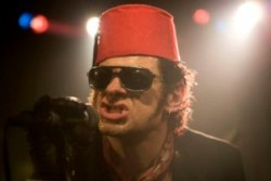 Photo of a man wearing a red fez. He's got sunglasses on too. It is Andy Serkis's face. 104 FIlms
