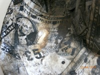 Detail from the image of the bowler hat showing a dollar bill and a £5 note