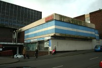 "Photo of a shabby 1970s square building with blue lines. The name of shop ""Martins dry cleaners, can just be made out."