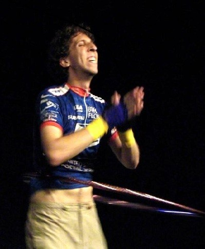 a man looks delighted and claps his hands as he spins a hoop around his waist