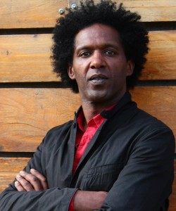portrait photo of author Lemn Sissay with folded arms against a wood panel background