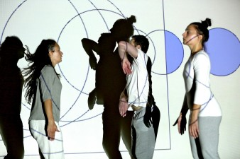 photo of three dancers in front of a projection showing a series of blue lines and circles against a white ground