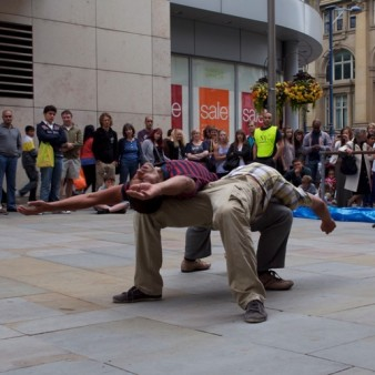 Photograph of two male dancers in a street bending over backwards supporting each other on the other dancer's thighs