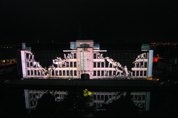 A photograph depicting Cork's College of Commerce with a projection which make it appear that the building is falling down