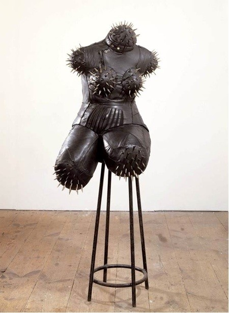 sculpture of a black female torso, without arms, legs or head, covered in spikes