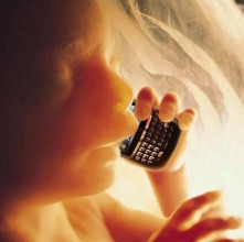image of a foetus inside a womb, holding a mobile phone