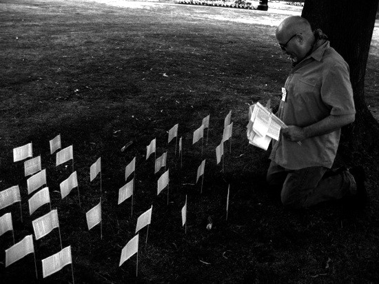 black and white photo of the artist Jon Adams amongst a field of flags