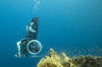 Side-on view of woman in wheelchair in tropical sea wearing summer. Her arms stretched out and looking up to the surface. Coral in the foreground and a shoal of fish in middle ground across the whole image.