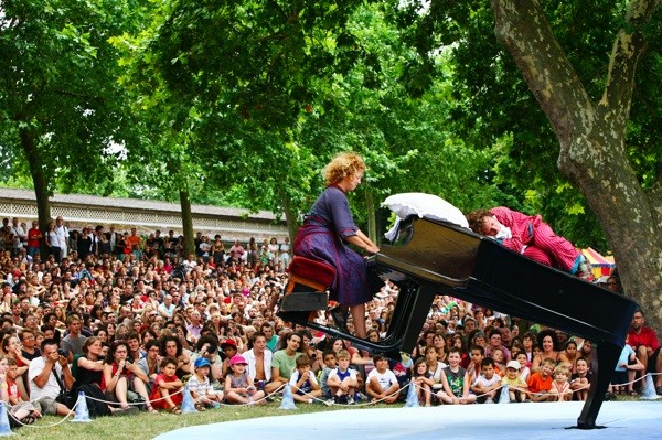 photo of a flying grand piano against the backdrop of a festival audience