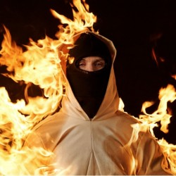 A photograph of Cassils' Inextinguishable Fire, showing the artist, in protective clothing covered in flames