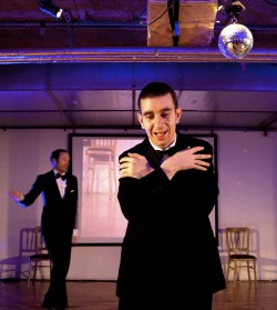 photo of Ian Johnston centre-stage, dressed in a suit, holding his arms around his shoulders, with Gary Gardiner in the background, also dressed in a black suit with a bow tie