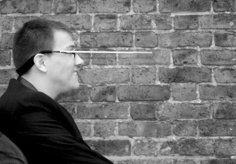 A black and white photograph of composer and conductor James Rose, in profile, with his specially designed head baton attached to his glasses. He is set against a brick wall