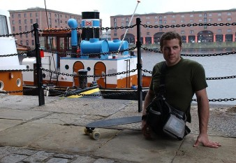 shows a man wearing t-shirt on a dockside. He has no legs, and is standing next to a skateboard