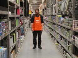 photo of performance artist Kim Noble dressed in orange B&Q supermarket overalls