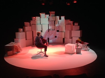 Julie McNamara on stage sitting on a chair within a white circular piece of flooring. She turns to face a large projection of her mum, Shirley, against a backdrop of large cardboard boxes