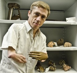 photo of performing artist Mat Fraser standing in front of a series of shelves containing prosthetic limbs