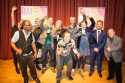 A photograph taking at the Oska Bright 2015 awards ceremony featuring several of the winners and presenters holding their awards aloft