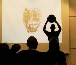 photo of poet Vince Laws with a motorbike helmet above his head, with an image of the object, painted with words, projected behind him