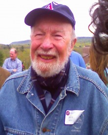 photo of Pete Seeger smiling at the camera, wearing a blue baseball hat