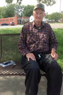 photo of an elderly man sitting on a bench on 16th Street, Kansas City