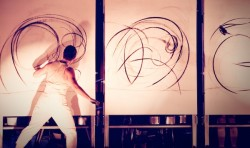 photo of artist / performer Rachel Gadsden moving between three large canvases