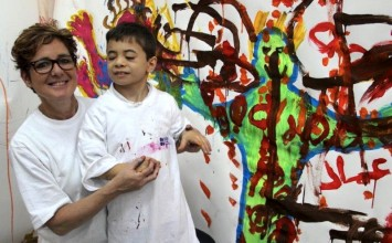 the artist Rachel Gadsden and a visually-impaired child are dressed in white t-shirts, posing in front of a painting mural