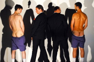 photo of the backs of a group of four men. two are dressed in suits and two show their bottoms