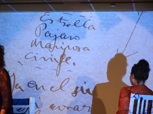 performer Isolte Avila stares with her back to a projection showing hand-written words in Spanish