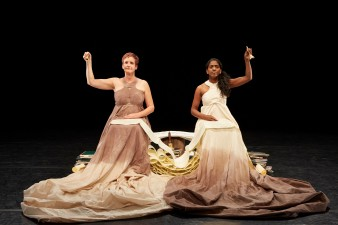 A photograph of Sue MacLaine's play Can I Start Again Please depicting Sue MacLaine and Nadia Nadarajah in long dresses each ringing a bell with scrolled up paper and books between them.