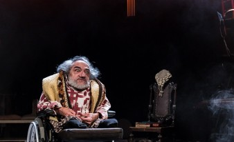 actor nabil shaban has wild grey hair and beard and wears a gold waistcoat