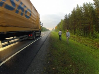 photo of two actors standing on the side of a busy road as a container lorry whizzes past them