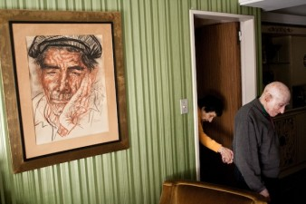 A photo of an elderly man leading a disabled woman by the hand into a living room with a large, framed portrait drawing on the wall.