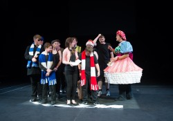 A photograph of a group of young disabled performers they are all wearing football style scarves.