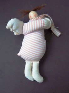 A rosy cheeked, overstuffed fabric angel in a candy-pink striped dress and scarf. She has fat little wings and two bristly tufts of brown hair.