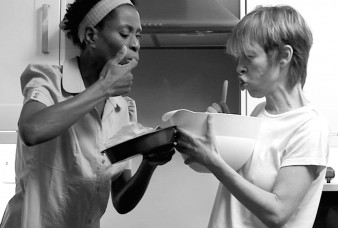 black and white still of two women eating cake mix from a bowl