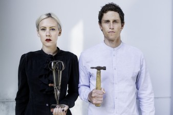 A photograph from the play Fake it 'til you Make it, featuring Bryony Kimmings and Tim Grayburn. The former is holding a whisk, the latter has a hammer.