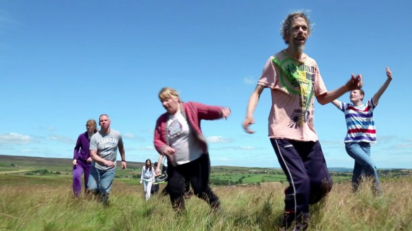 photo of Jez Colborne and the cast from Contained in a field under a blue sky